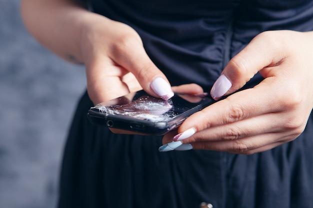 壊れた電話を保持している若い女性