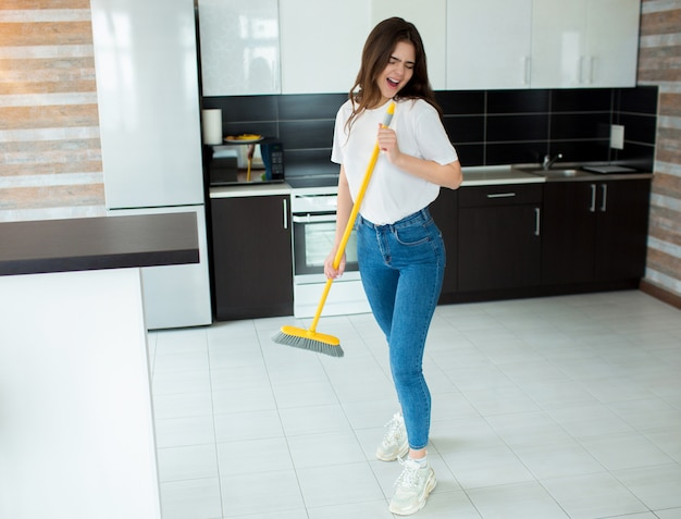 Young woman holding broom in hands and singing out loud.
