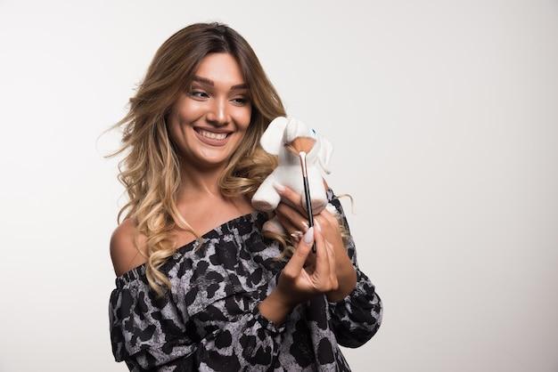 白い壁にブラシと象のおもちゃを保持している若い女性。