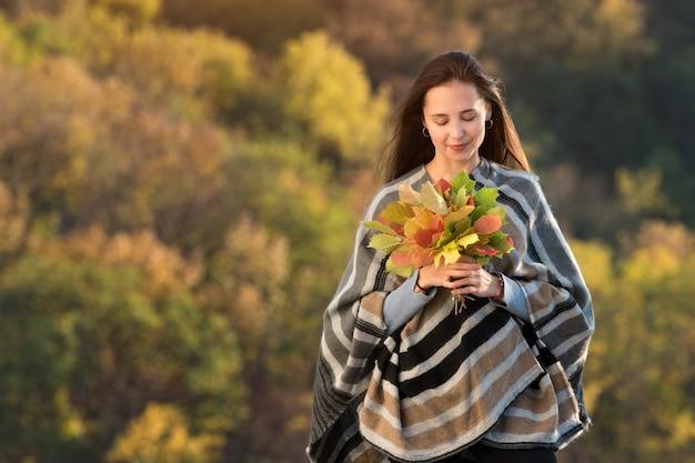 Молодая женщина, держащая букет осенних листьев