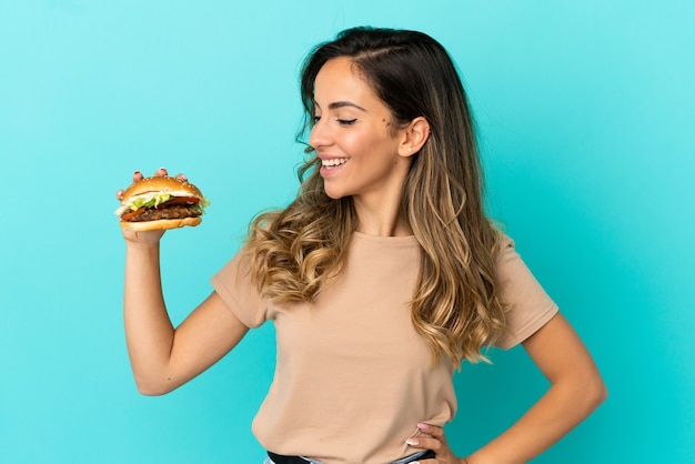Young woman holding a burger over isolated background looking side