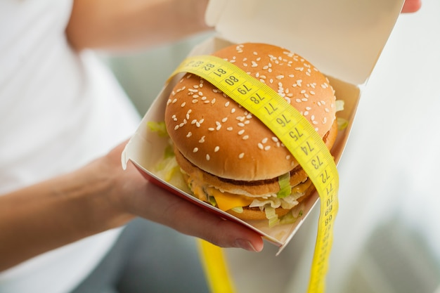 A young woman holding a burger in a measuring tape
