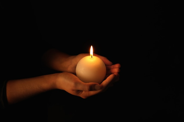 Young woman holding burning candle in darkness
