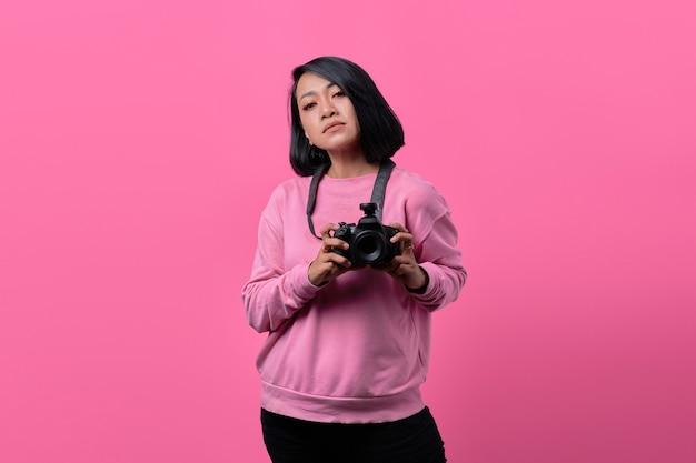 フラットな表情でカメラを保持している若い女性