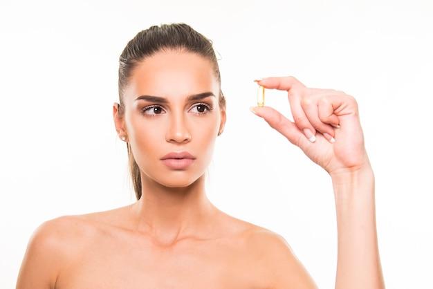 Молодая женщина, держащая капсулу коллагена. концепция молодой здоровой кожи, витаминов, пищевых добавок, здорового образа жизни.