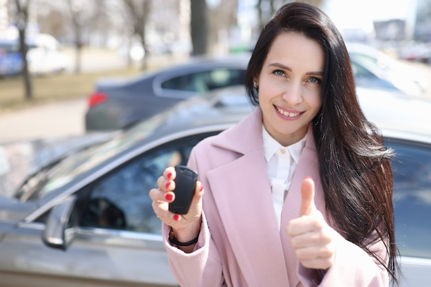 Молодая женщина держит ключи от машины и показывает палец вверх