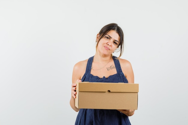 Young woman holding cardboard box in dress and looking confident