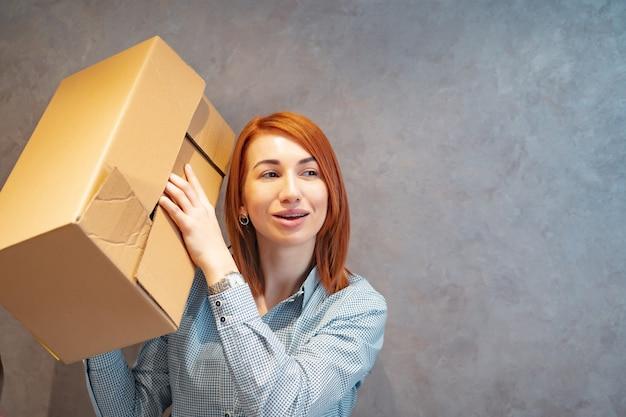 Молодая женщина держит картонные коробки и трясет его