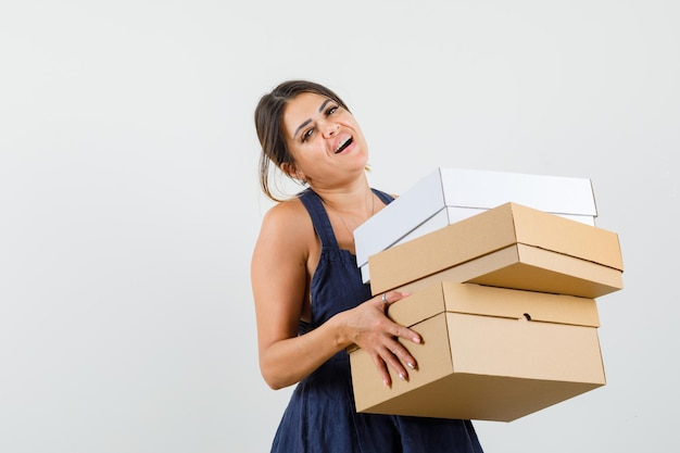 Young woman holding cardboard boxes in dress and looking jolly