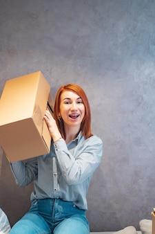 Young woman holding cardboard boxes and shakes it