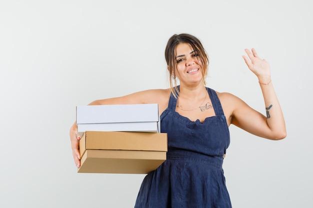 Молодая женщина держит картонные коробки, машет рукой в платье и выглядит весело