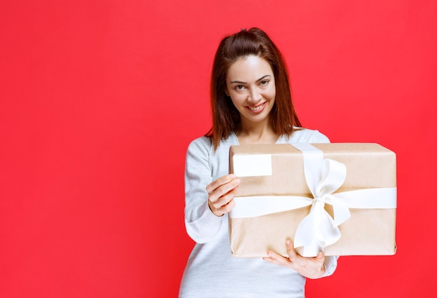 Giovane donna che tiene una scatola regalo di cartone e presenta il suo biglietto da visita