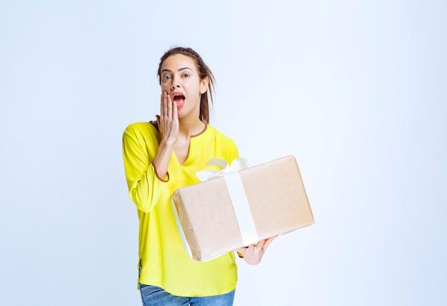 Giovane donna che tiene in mano una scatola regalo di cartone e pensa al mittente sconosciuto