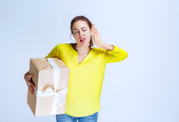 Giovane donna che tiene in mano una scatola regalo di cartone e pensa attentamente
