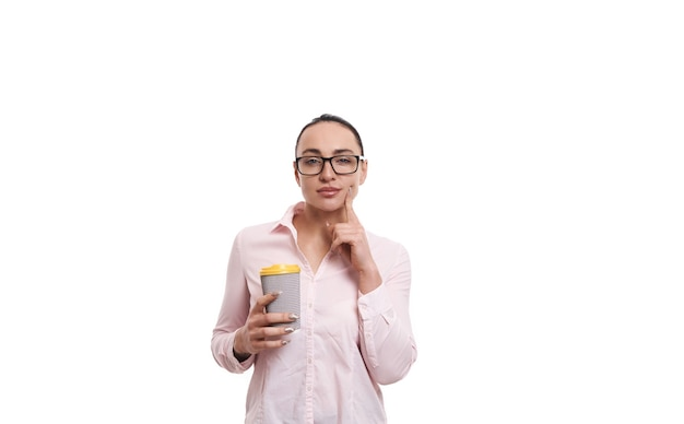 Young woman holding a cardboard recyclable paper cup with hot drink and posing on white background with copy space .