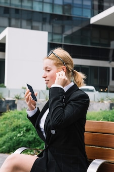 Young woman holding cell phone in hand talking on wireless bluetooth