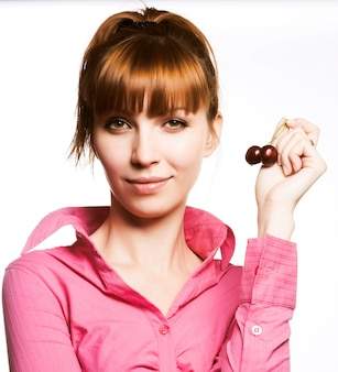 Young woman holding cherry, close up