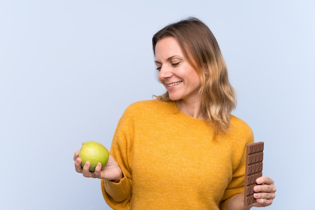 Young woman holding chocolate and an apple