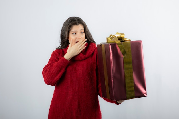 白い壁にクリスマスプレゼントを持っている若い女性。