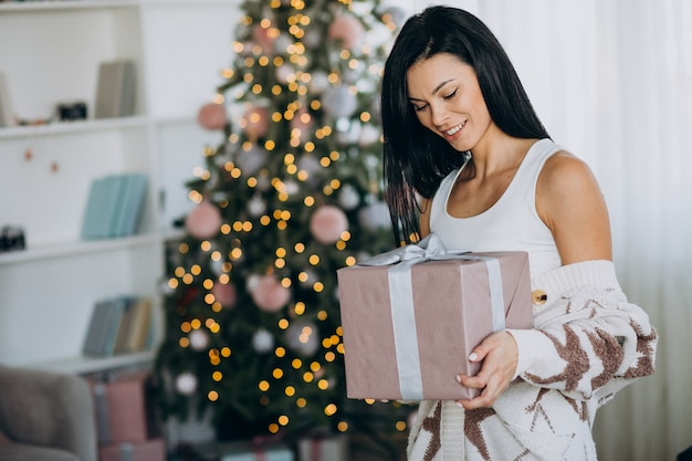 Молодая женщина, держащая рождественский подарок на елку