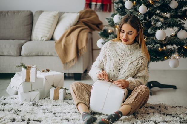 Giovane donna che tiene i regali di natale e che si siede sotto l'albero di natale
