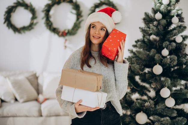 Молодая женщина, держащая рождественские подарки