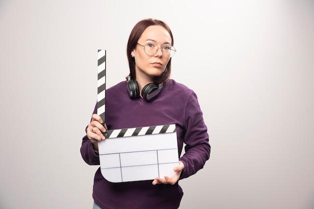 Giovane donna che tiene un nastro del cinema su un bianco. foto di alta qualità