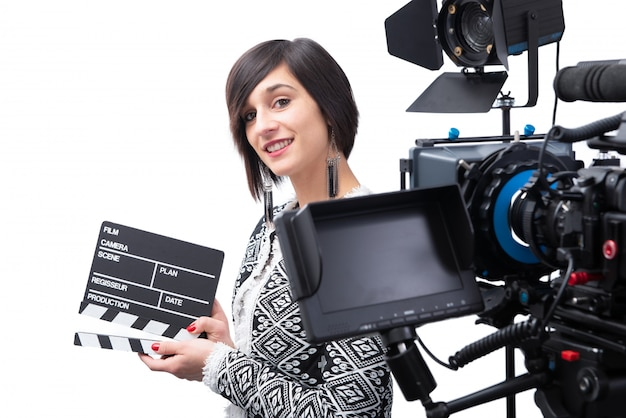 Young woman holding a clapboard.