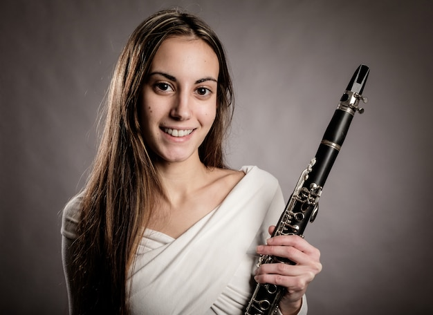 Young woman holding a clarinet on a gray