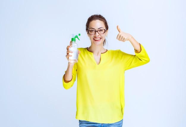 Giovane donna che tiene in mano uno spray detergente e mostra un segno di divertimento