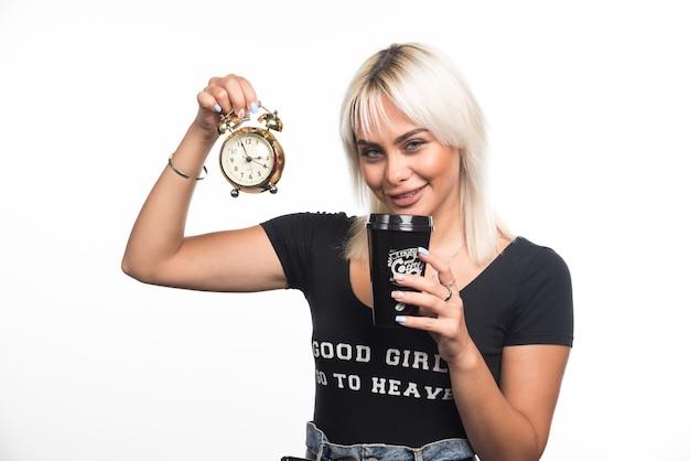 Молодая женщина, держащая часы и чашку кофе на белой стене.