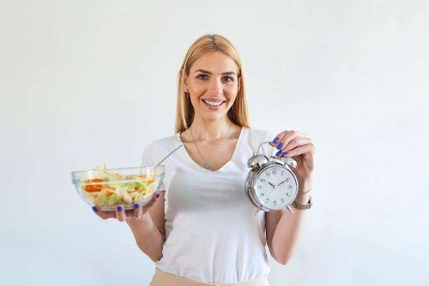시계와 샐러드의 건강 식품을 들고 젊은 여자 간헐적 단식 개념입니다. 체중 감량, 식사 조절 또는 다이어트 개념에 대한 시간.