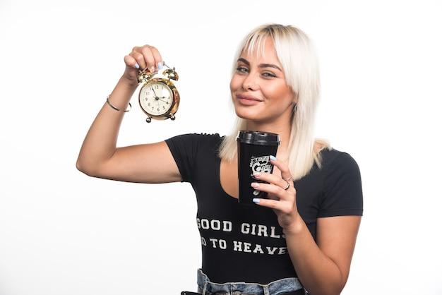 Giovane donna che tiene orologio e tazza di caffè sul muro bianco.