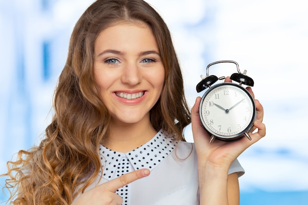 Young woman holding a clock. time management concept