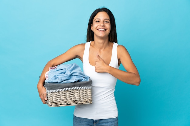 Young woman holding a clothes basket giving a thumbs up gesture