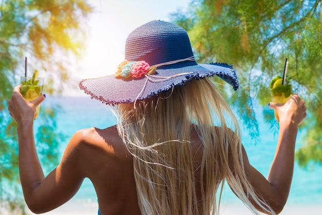 ビーチで彼女の手でカクテルを保持している若い女性