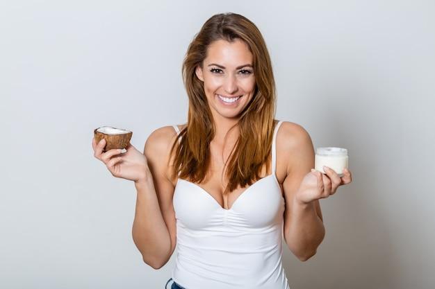 Молодая женщина держит бутылку кокоса и сливок