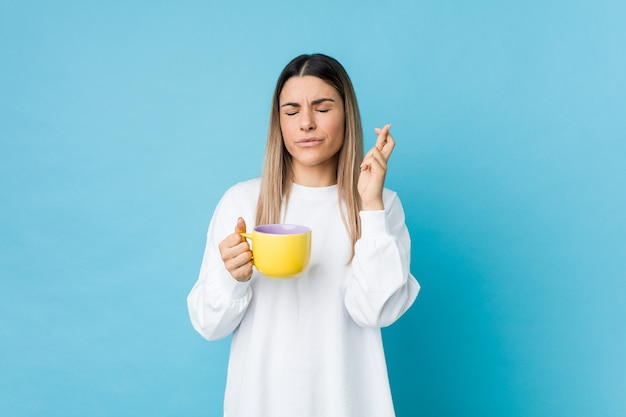 Young woman holding a coffee cup crossing fingers for having luck
