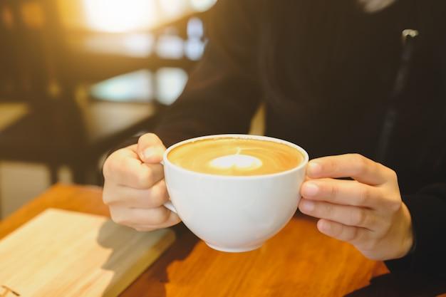 カフェショップ内のコーヒーカップを保持している若い女性。