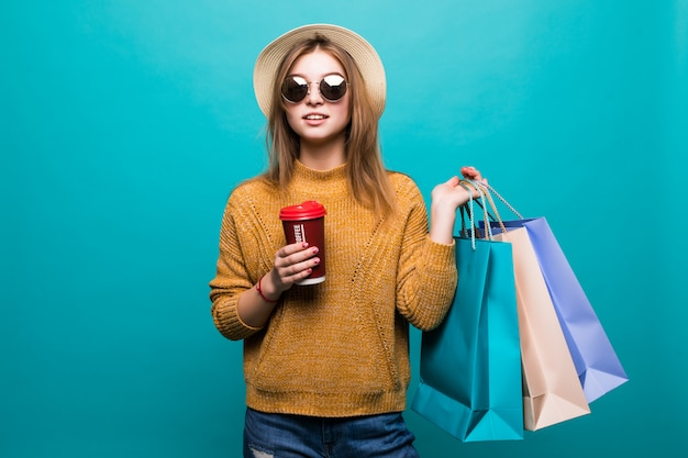 Young woman holding coffee to go and shopping bags while smiling on blue wall