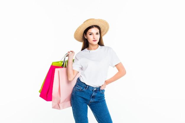 Giovane donna che giudica le borse variopinte isolate sulla parete bianca
