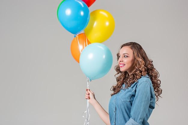 Giovane donna che tiene palloncini colorati sulla parete grigia dello studio
