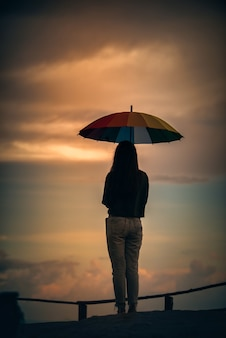 Молодая женщина держит красочный зонтик, глядя на дождь в горах с драматическим небом на закате