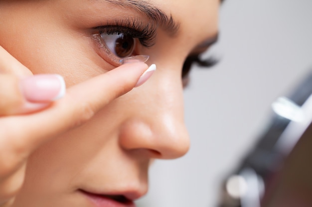 Young woman holding contact lens on finger.