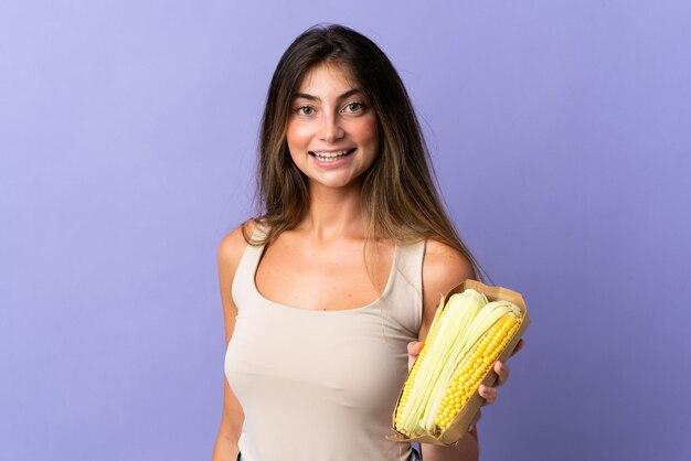 Молодая женщина, держащая кукурузу, изолирована на фиолетовом, много улыбается