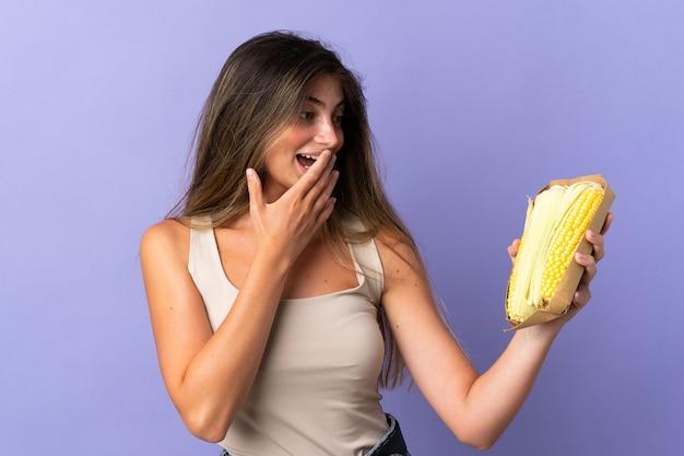 Молодая женщина держит кукурузу, изолированную на фиолетовом, с удивленным и шокированным выражением лица