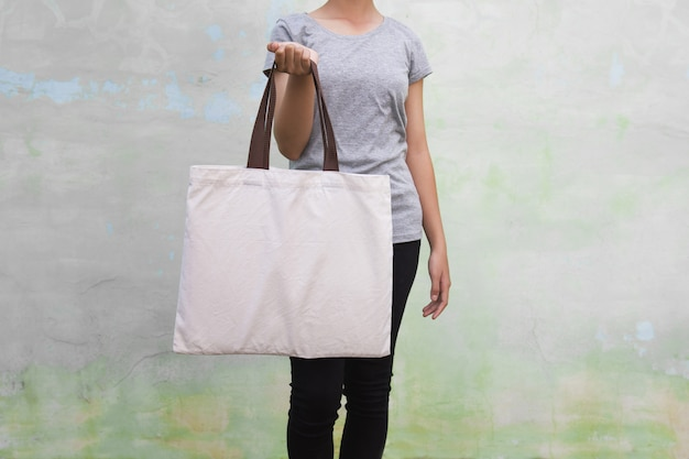 Молодая женщина держа сумку хлопка на предпосылке стены. эко концепция