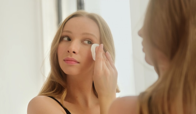 Young woman holding cotton pad disk cleaning face skin with cleanser tonic