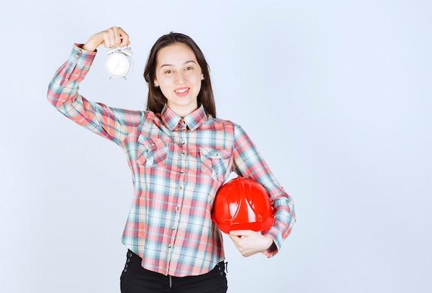 Una giovane donna che tiene il casco e una sveglia. Foto Gratuite
