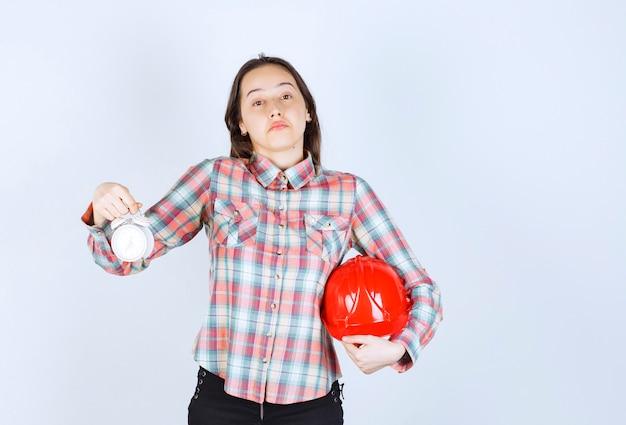 Una giovane donna che tiene il casco e una sveglia.